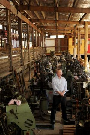 Peter Crisp stands amongst some sock making machine's that sit in his restored Shearing Shed that he hopes will become ...