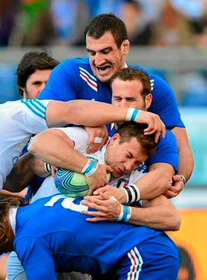 Italy's centre Tommaso Benvenuti is tackled by France's fly-half Frederic Michalak and lock Yoann Maestri.