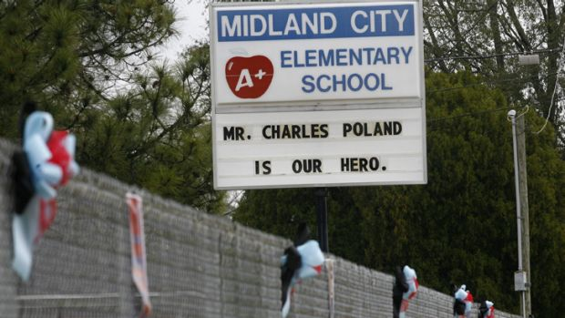 A sign and wreaths honouring murdered bus driver Charles Poland, Jr. at Midland City Elementary School.