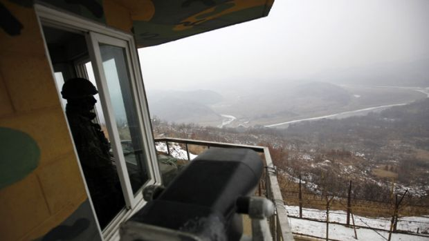 A waiting game ... a South Korean soldier looks over the DMZ to North Korea.