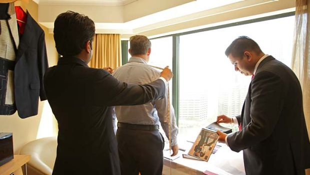 Suits you … Martin Raja, left, and Harry Menon from Raja Fashions of Hong Kong take the measurements of a Sydney ...