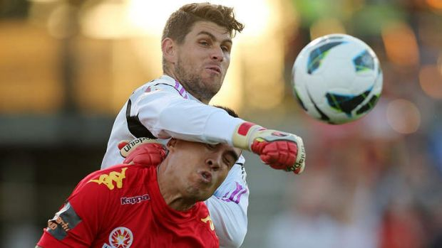 Squaring up: Victory's Nathan Coe makes a save under pressure over Adelaide's Iain Ramsay.