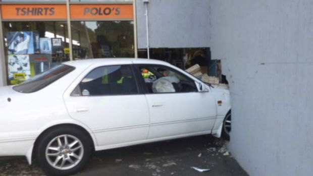 "A car smashed into the ""Action Sports Wear"" shop front wall early Saturday."