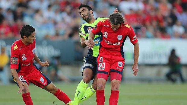 Target: Marcos Flores (centre) was hounded by Adelaide, this time the tackler was Jonathan McKain, right.