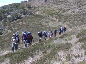 The group of young people trek down a mountain.