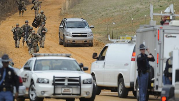 Heavily armed men move away from the home of Jimmy Lee Dykes in Midland City, Alabama during the siege in January.