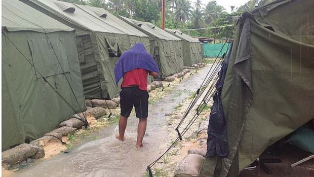 An asylum seeker walks through water running between rows of tents.