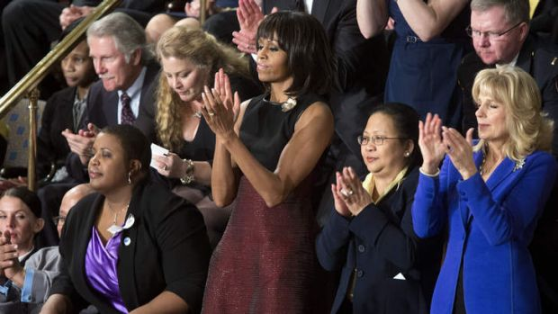 First Lady Michelle Obama applauds.