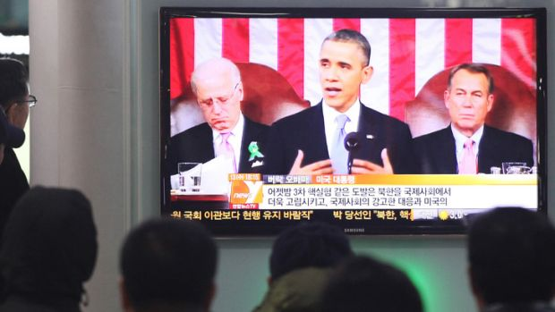People watch a television news report on U.S. President Barack Obama's State of the Union address at Seoul Railway ...
