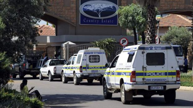 Police vehicles enter the private townhouse complex where Oscar Pistorius lives.