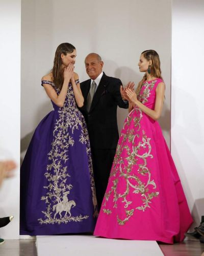 Designer Oscar De La Renta (C) smiles with models after presenting his Autumn/Winter 2013 collection.