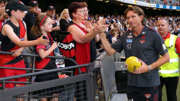Coach James Hird slaps hands with a Bombers supporter after their win in the round one AFL NAB Cup.