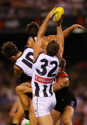 Travis Cloke of the Magpies marks the ball against the Bombers.