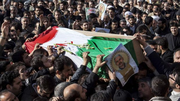 Iranian mourners carry the flag draped coffin of Hassan Shateri in Tehran.