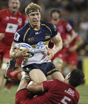 David Pocock of the Brumbies is tackled by Rob Simmons of the Reds.
