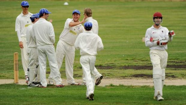 Queanbeyan players celebrate the wicket of Wests' Darren Richards at Freebody Oval.
