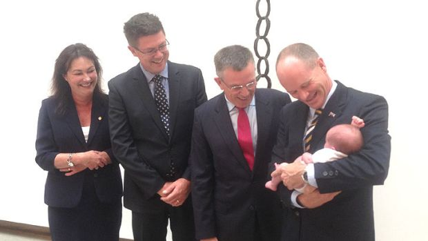 Premier Campbell Newman holds Alice, the newborn daughter of his chief of staff, Ben Myer, while Ian Walker (second from ...