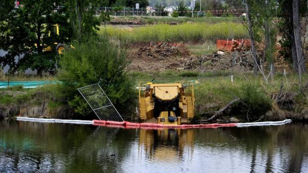A bulldozer has been submerged in water at the Molonglo River what is thought to be an act of vandalism .