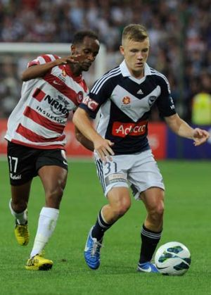 Scott Galloway of Victory guards the ball as Youssouf Hersi of the Wanderers approaches.