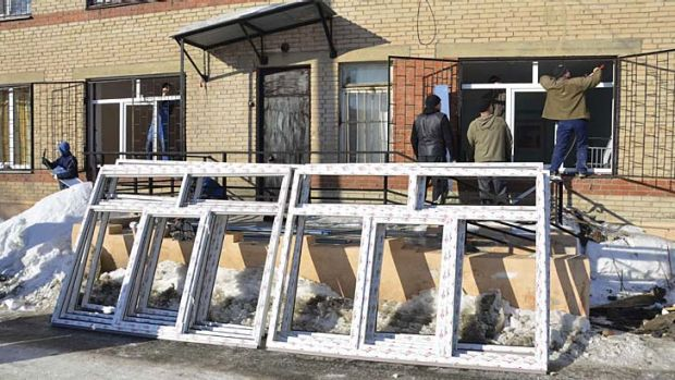 Employees try to fix windows of a maternity ward which was damaged by a shockwave from a meteorite.