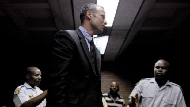 Henke Pistorius reaches out to his Olympic athlete son, Oscar, during his court hearing.
