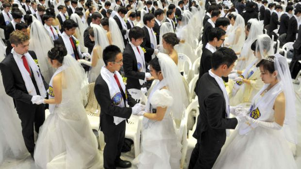 Newly-married couples hold hands to pray during a mass wedding organised by the Unification Church.