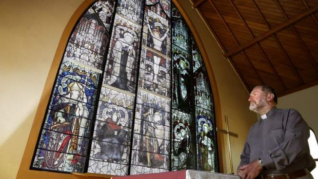 Father Michael Faragher at All Saints Anglican Church in Ainslie in front of a facsimile of the Sheffield Stain Glass ...