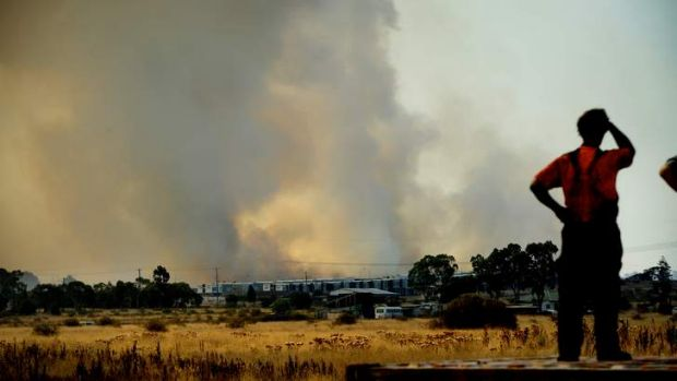 A worker ponders what might be as fire approaches Epping.