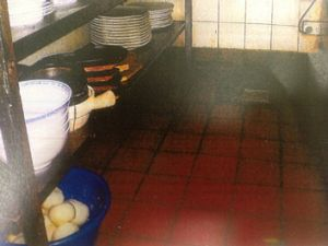 Unclean shelving and food containers stored on the floor.