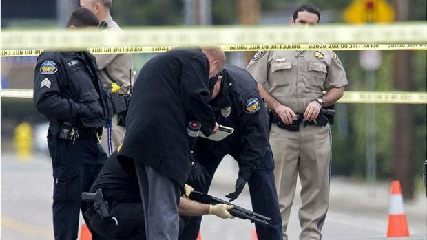 Police investigators examine a gun laying in the street in Orange, California, near where a body laid moments before.