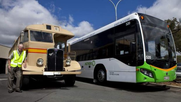 Bus conductor Eddie Carnall standing next to a vintage 1949 AEC Regal Omnibus, alongside a 2013 ACTION bus.