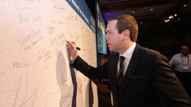 AWU chief Paul Howes signs his name to a pledge to stop Tony Abbott in his tracks at the union's conference in ...