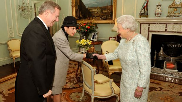 Queen Elizabeth II shakes hands with Sasha Rann as her husband High Commissioner of Australia Mr Mike Rann looks on in a ...
