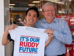 Dressing the troops … Kevin Rudd gives a shirt to supporter Jibrail Idris in Brisbane.