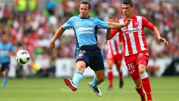 Catcalls and venom from the crowd … Lucas Neill, who spurned Heart's advances, competes for the ball against Eli ...