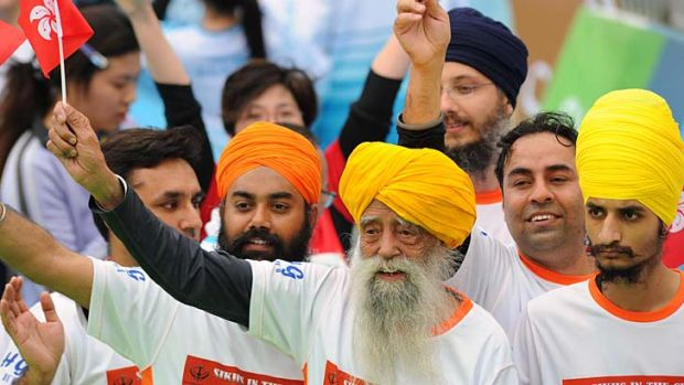 Indian-born British national Fauja Singh (centre) waves a Hong Kong flag after crossing the finish line in the 10-km ...