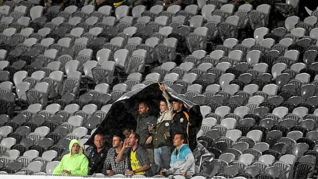 Where are you ... fans brave the wet weather during the match against the Victory.