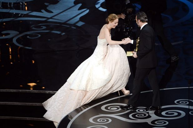 Jennifer Lawrence walks on stage to accept the Oscar from Jean Dujardin (best actor for <i>The Artist</i> in 2012).
