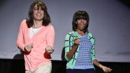 This image released by NBC shows host Jimmy Fallon dressed as a mom, left, dancing with first lady Michelle Obama during ...