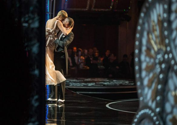 Actors Channing Tatum and Charlize Theron dance onstage.