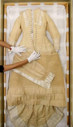 Conservator of Costumes Textiles and Dress, Suzanne Chee, shows a 1882, wool and silk wedding dress, worn by Hannah ...