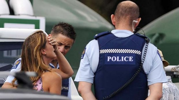 Police comfort a woman believed to be a family member of the victim.