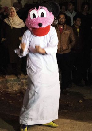 "Egyptian youth perform the Internet craze, the ""Harlem Shake"" in a Mickey Mouse mask."