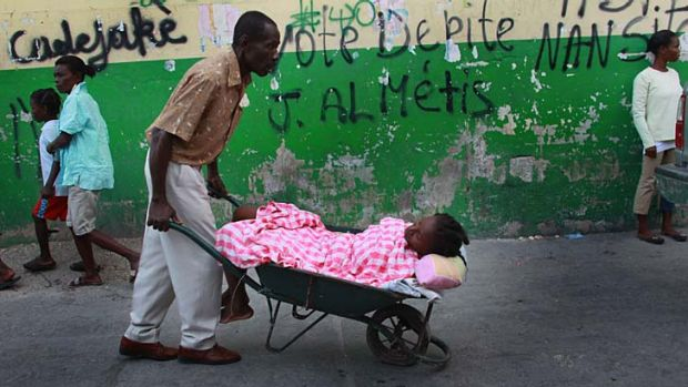 Harsh reality … a person with cholera is carted to doctors in Haiti.