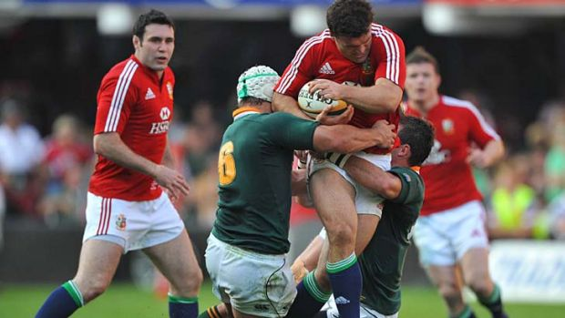 Jamie Roberts of the British and Irish Lions is tackled by Heinrich Brussow and Ruan Pienaar of the Springboks.
