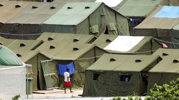 A refugee wonders through the rows of temporary tents at the Nauru detention centre.