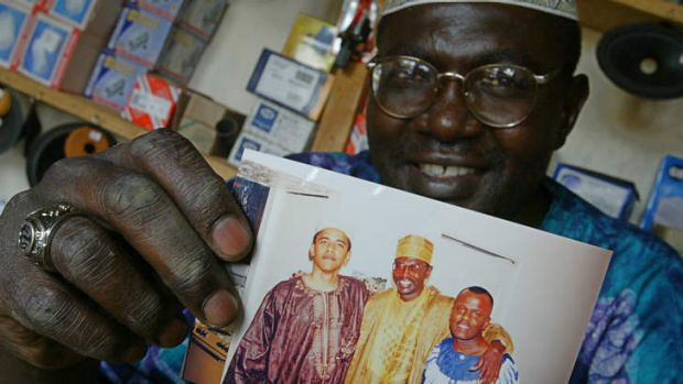 Malik Obama holding a photo of himself with half-brother Barack Obama.