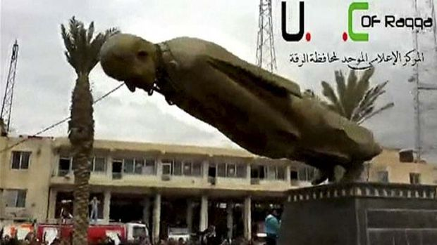 A statue of President Bashar Al-Assad's father, Hafez Al-Assad, is torn down after Syrian opposition fighters captured ...