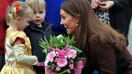Britain's Catherine, Duchess of Cambridge receives flowers from 3-year old Isobelle Laursen, left, during her visit to ...