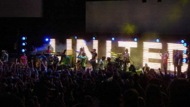 Hillsong United playing onstage to followers.